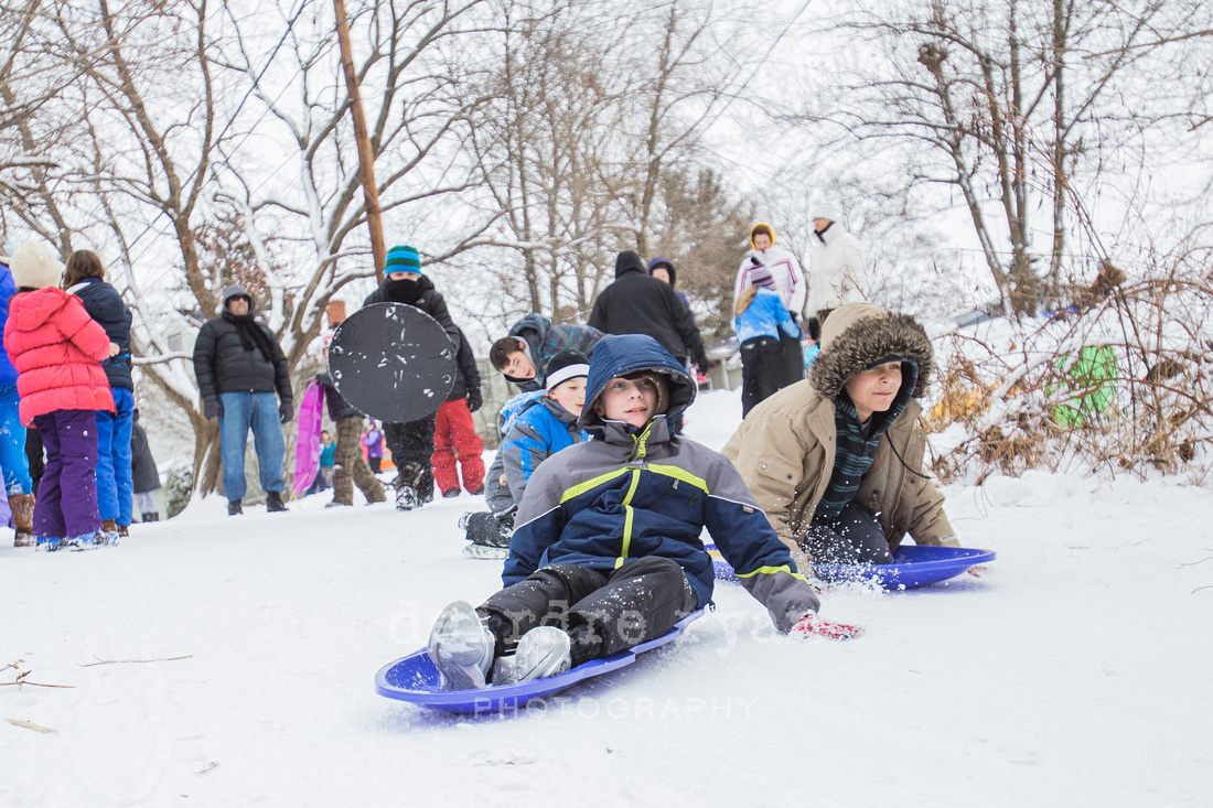 Children sledding down a hill on a snow day from school. Photo by Deirdre Ryan Photography